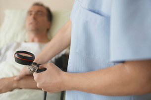 Nurse Taking blood pressure and pulse of patient in hospitalの写真素材 [FYI03641183]