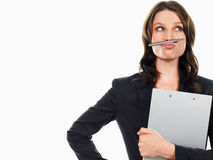 Businesswoman pulling funny face with penの写真素材 [FYI03641211]