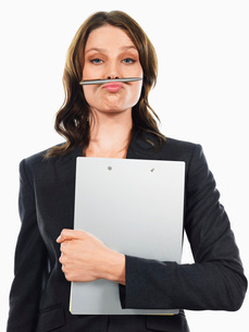 Businesswoman pulling funny face with penの写真素材 [FYI03641212]