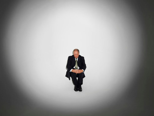 Businessman sitting under the spotlightの写真素材 [FYI03641237]