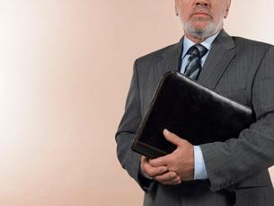 Businessman Holding Leather Binder half length croppedの写真素材 [FYI03641239]