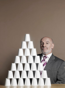 Businessman sitting by pyramid of plastic cupsの写真素材 [FYI03641248]