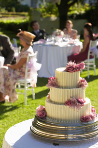 Wedding cake guests at tables in backgroundの写真素材 [FYI03641265]