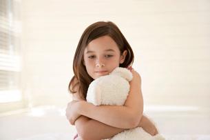 Girl cuddling teddy bear sitting on bed half lengthの写真素材 [FYI03641272]