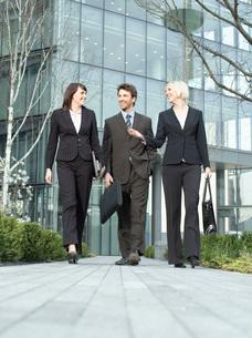 Three business people walking outside office building talkinの写真素材 [FYI03641278]