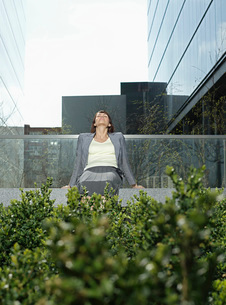 Mid adult businesswoman relaxing on wall outside office builの写真素材 [FYI03641284]