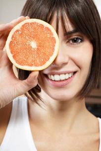 Woman holding half of grapefruit in front of face portrait cの写真素材 [FYI03641308]