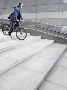 Business man wearing crash helmet riding bicycle down stepsの写真素材 [FYI03641310]