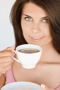 Portrait of young woman holding cup of tea with lemonの写真素材 [FYI03641326]