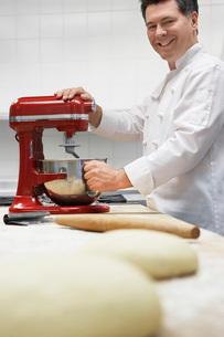 Chef using dough mixer in kitchen portraitの写真素材 [FYI03641331]