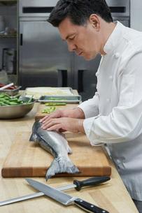 Male chef preparing salmon in kitchenの写真素材 [FYI03641332]