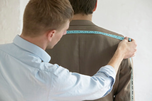 Tailor measuring jacket on man back view close upの写真素材 [FYI03641370]