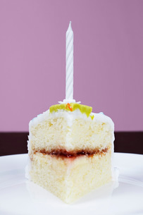 Slice of cake with birthday candle close-upの写真素材 [FYI03641410]