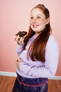 Overweight girl (13-15) smiling holding brownie hand on bellの写真素材 [FYI03641634]