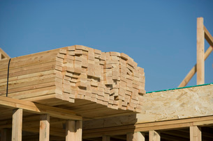 Wooden planks stacked on house constructionの写真素材 [FYI03641666]