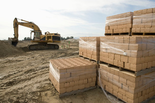 Digger and stacked bricks on construction siteの写真素材 [FYI03641680]