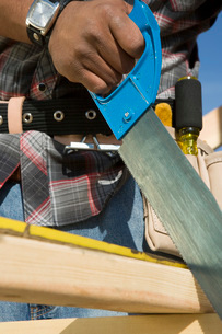 Construction worker sawing on construction siteの写真素材 [FYI03641684]