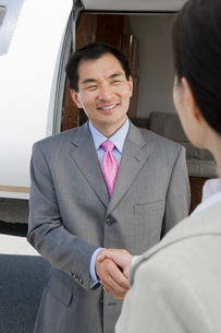 Mid-adult Asian businessman shaking hands with mid-adult busの写真素材 [FYI03641687]