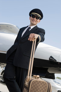 Asian male pilot leaning at suitcase in front of airplane elの写真素材 [FYI03641700]