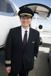 Asian male pilot in front of airplane elevated view.の写真素材 [FYI03641702]