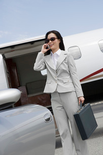 Mid-adult businesswoman using mobile phone in front of airplの写真素材 [FYI03641711]