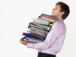 Male office worker carrying heavy binders on white backgrounの写真素材 [FYI03641731]