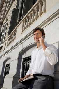 Businessman using mobile phone by high-rise buildingの写真素材 [FYI03641752]