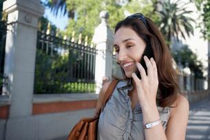 Woman using cell phone on sidewalkの写真素材 [FYI03641753]