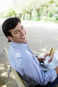 Businessman with sandwich and newspaper sitting on park bencの写真素材 [FYI03641765]