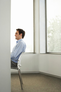 Businessman sitting on chair in office side view half lengthの写真素材 [FYI03641778]