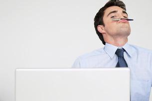 Businessman balancing pen on upper lipの写真素材 [FYI03641781]