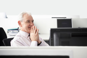Mature businessman sitting with folded hands in office cubicの写真素材 [FYI03641809]
