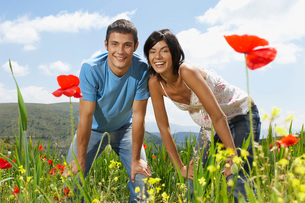 Young couple standing in mountain meadow portrait front viewの写真素材 [FYI03641821]