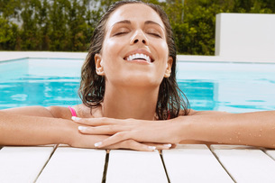 Woman in Swimming Pool resting on poolside close up ground vの写真素材 [FYI03641830]