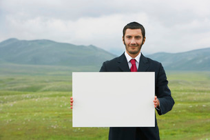 Smiling businessmen standing in mountain field holding blankの写真素材 [FYI03641838]