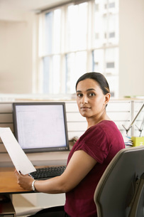 Mid-adult female office worker at cubicle holding paperworkの写真素材 [FYI03641868]