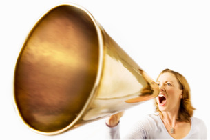 Woman shouting through megaphone studio shotの写真素材 [FYI03641890]