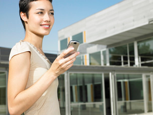 Smiling young woman standing in plaza sending text messageの写真素材 [FYI03641912]