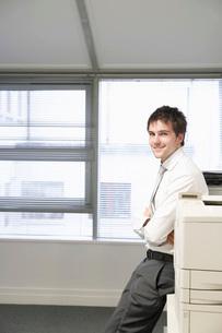 Businessman leaning against office photocopier portraitの写真素材 [FYI03641943]