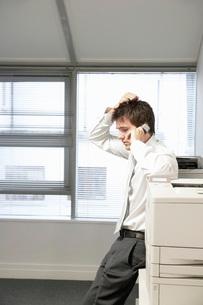 Uncertain Businessman leaning on office photcopierTalking onの写真素材 [FYI03641944]