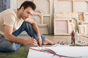 Artist Working on Canvas on Floor of Studioの写真素材 [FYI03641952]