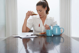 Woman with stain on blouse at dining room tableの写真素材 [FYI03641976]