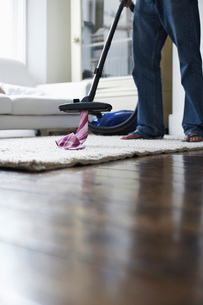 Man vacuuming tie from rug low sectionの写真素材 [FYI03641978]