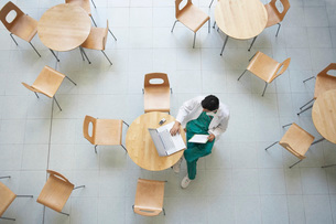Physician Using Laptop in cafeteria view from aboveの写真素材 [FYI03642030]