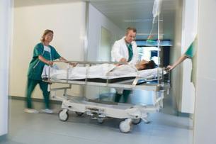 Doctors Moving Patient on gurney through hospital corridorの写真素材 [FYI03642033]