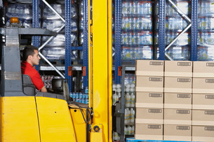 Warehouse Worker Operating Forklift side viewの写真素材 [FYI03642049]