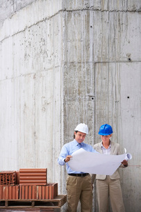 Construction manager and architect examining plans on siteの写真素材 [FYI03642054]