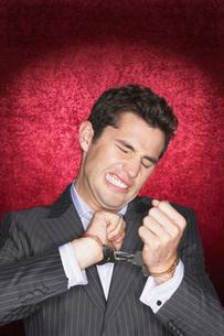 Man straining in handcuffs against red velvet backgroundの写真素材 [FYI03642071]