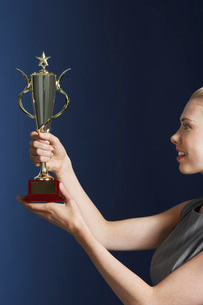 Woman holding and admiring trophy against dark background prの写真素材 [FYI03642075]