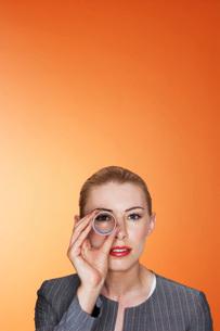 Woman looking through paper tube against orange backgroundの写真素材 [FYI03642083]